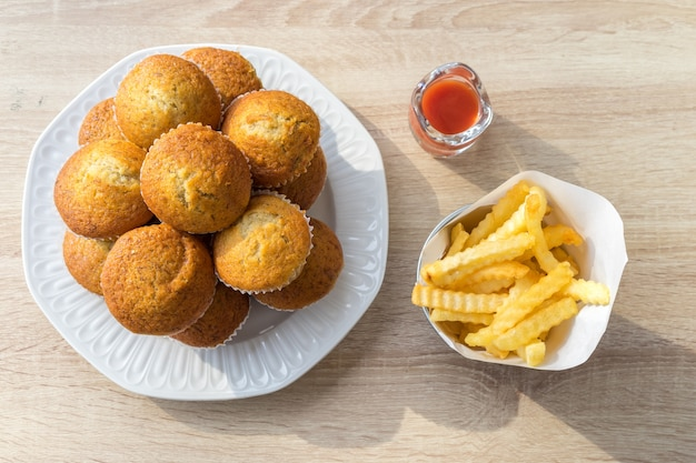 Top de muffins de banana, batatas fritas e ketchup na mesa de madeira no restaurante.
