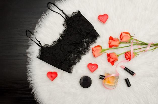 Top de renda preta, buquê de rosas laranja, velas, perfume