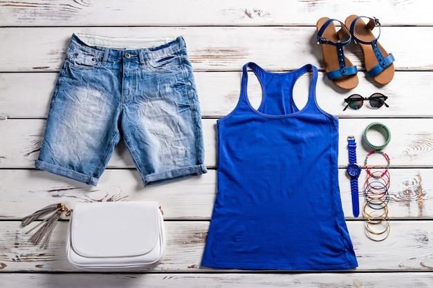 Top e shorts de mulher. guarda-roupa feminino em fundo de madeira. roupa leve de verão feminino. bela roupa de verão com acessórios.