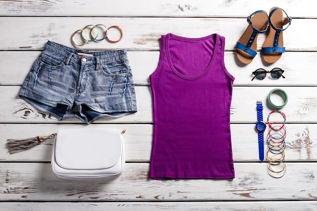 Top e shorts roxos de mulher. roupas elegantes na prateleira velha. roupa de senhora com top roxo. roupa para a estação quente para senhoras.