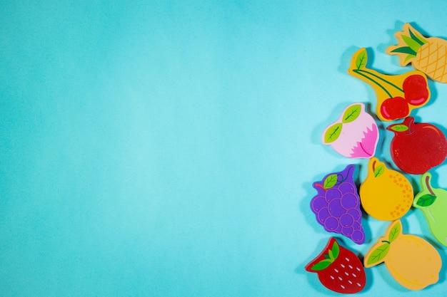 Top of view brinquedos de madeira com frutas em fundo azul