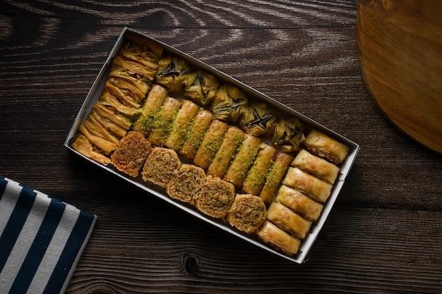 Top of view massa doce baklava turca com caixa e tábua de madeira