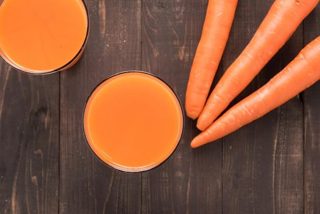 Top shot suco de cenoura fresca no fundo de madeira