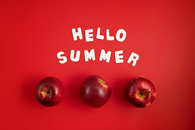 Top veiw de maçãs frescas e suculentas e texto olá verão na parede vermelha. no verão, frutas vermelhas, vitaminas, compre o conceito de frutas orgânicas locais. postura plana, copie o espaço
