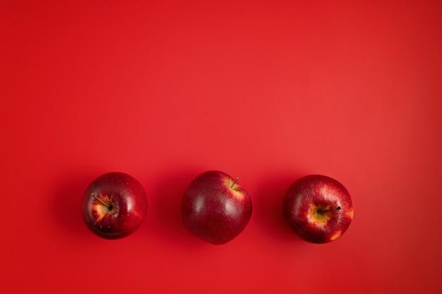 Top veiw de maçãs frescas e suculentas na parede vermelha. no verão, frutas vermelhas, vitaminas, compre o conceito de frutas orgânicas locais. postura plana, copie o espaço