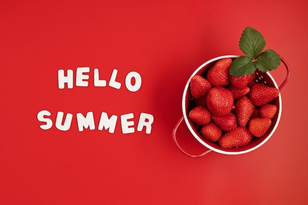 Top veiw de morango fresco e suculento e texto olá verão na parede vermelha. no verão, frutas vermelhas, vitaminas, compre o conceito de frutas orgânicas locais. postura plana, copie o espaço