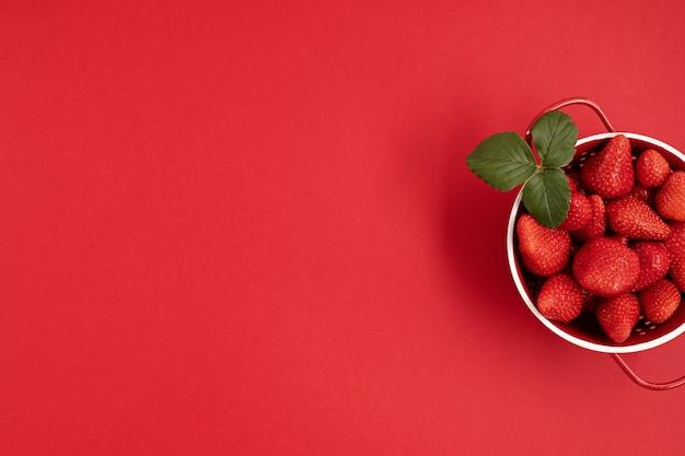 Top veiw de morango fresco e suculento na parede vermelha. no verão, frutas vermelhas, vitaminas, compre o conceito de frutas orgânicas locais. postura plana, copie o espaço