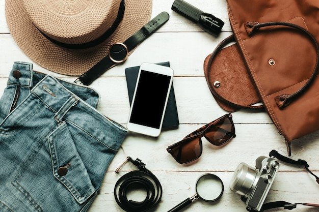 Top view acessórios para viajar com roupas femininas conceito.blanco