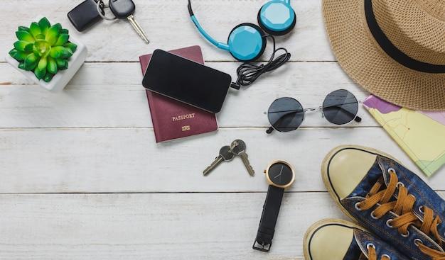 Top view acessórios para viajar conceito. telefone móvel, ouvindo música por fone de ouvido em fundo de madeira. sapatos, passaportes, relógios, óculos de sol e chapéu na mesa de madeira.