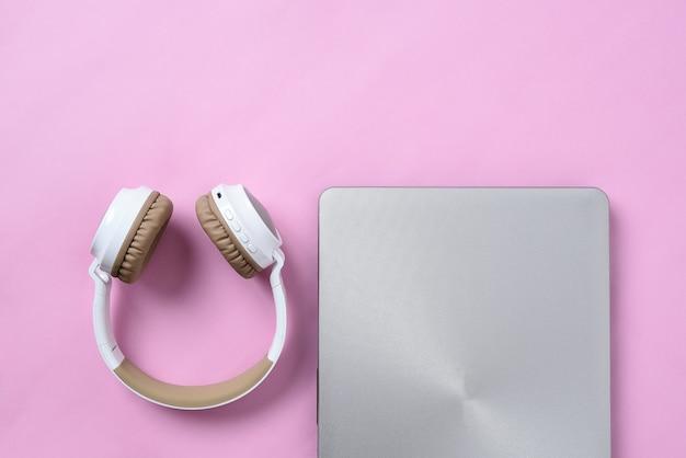 Top view flatlay de fone de ouvido sem fio moderno e laptop minimalista no espaço de trabalho cor-de-rosa