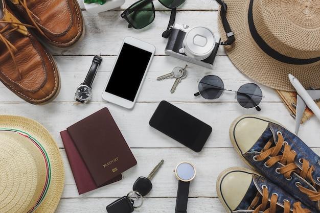 Top view mulheres e acessórios de homem para viajar concept.white e celular preto, avião, chapéu, passaporte, relógio, óculos de sol, sapatos e chave na mesa de madeira.