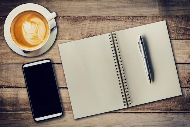 Top view notebook, caneta, xícara de café e telefone na mesa de madeira, filtro vintage.