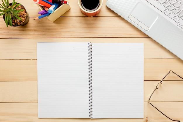 Top view notebook, lápis, café preto, cactus, relógio, nota papper, estacionário, caneta no fundo do escritório.