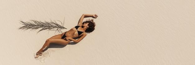 Top vista aérea de drone de mulher em biquíni de maiô relaxando e tomando banho de sol na praia