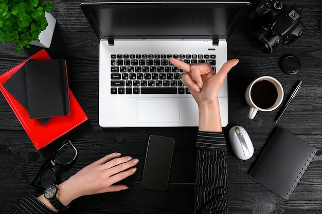 Tópico de negócios e tecnologia, a mão de uma mulher em uma camisa preta, mostrando um gesto contra o fundo ...