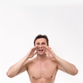 Topless homem gritando e olhando para a câmera