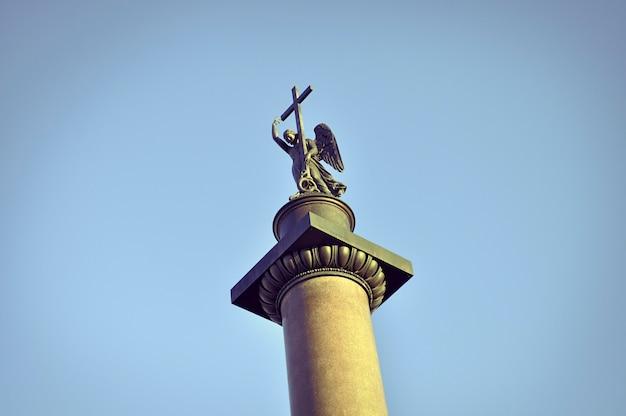 Topo da famosa coluna de alexandre, mostrando a estátua de um anjo segurando uma cruz. o monumento é colocado na praça do palácio de são petersburgo