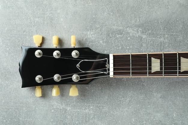 Topo da guitarra elétrica em plano de fundo texturizado cinza