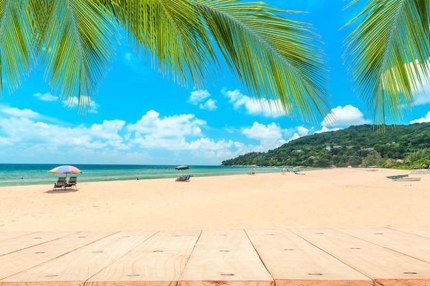 Topo da mesa de madeira na frente da praia branca.