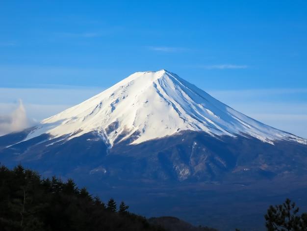 Topo da montanha fuji preenchido com neve branca e fundo de céu azul na cena de luz da manhã