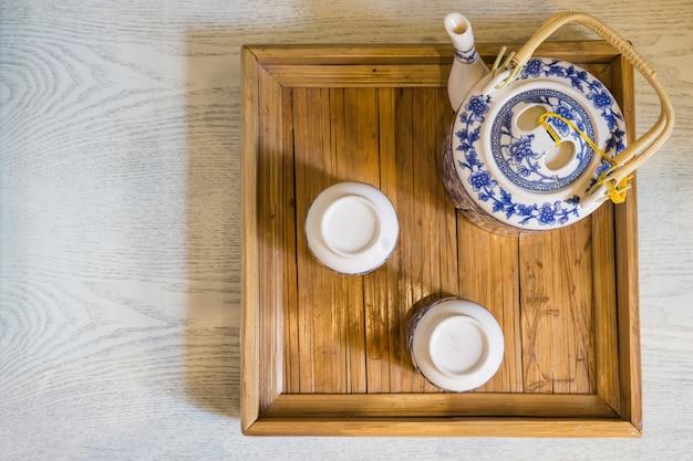 Topo da tradicional xícara branca de chá e bule em closeup de bandeja de madeira na mesa