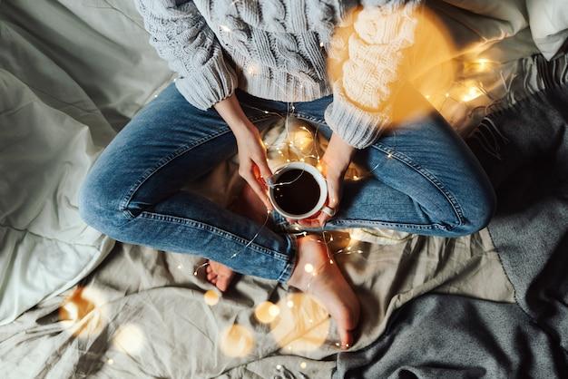 Topo da vista da mulher sentada na cama, segurando a xícara de café com luzes de natal e bokeh ao redor, foco seletivo raso