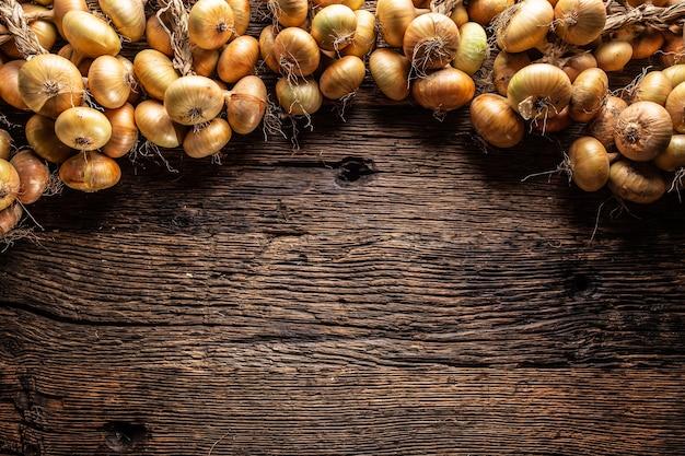 Topo da vista de muitas cebolas amarelas na mesa de madeira.