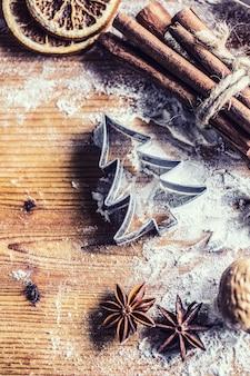 Topo da vista mesa de padaria cheia de ingredientes aromáticos de natal, anis estrelado, canela, laranja seca etc.
