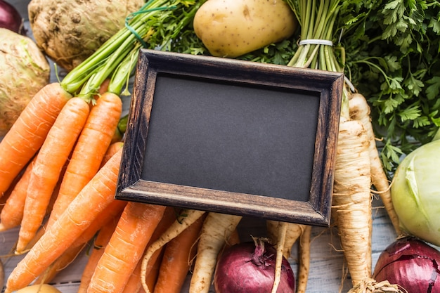 Topo da vista quadro-negro vazio sobre legumes frescos.