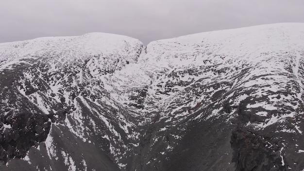 Topo de penhasco coberto de neve na rocha vulcânica de clima nublado do ártico