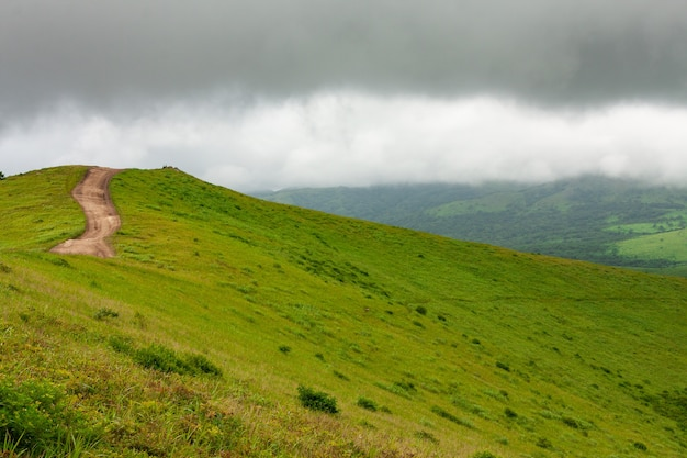 Topo de uma colina com uma estrada de terra sinuosa, paisagem de verão em tempo nublado.