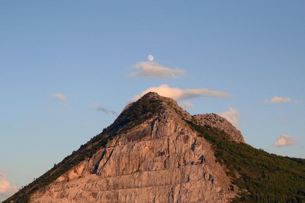 Topo de uma colina sob o céu brilhante
