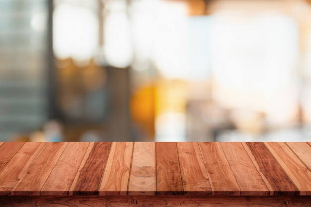 Topo vazio da mesa de madeira com desfoque de fundo de café ou cafeteria.