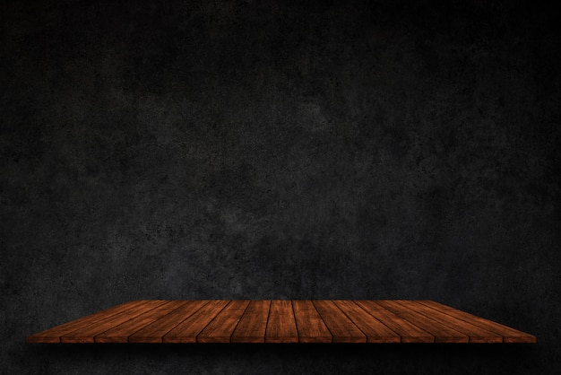 Topo vazio de prateleiras de madeira no fundo da parede de concreto escuro
