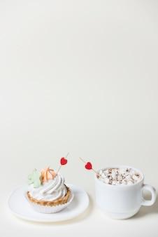 Toppers de coração vermelho no cupcake e xícara de café