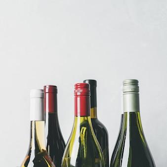 Tops de diferentes novas garrafas de champanhe, vinho branco, vermelho sobre fundo claro