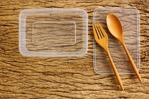 Topview, caixa de comida de plástico vazia flatlay em piso de madeira retrô. a caixa de plástico usada pode reciclar para economizar meio ambiente e energia.
