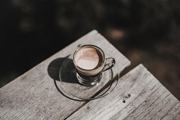 Topview de hot americano café em um copo colocado sobre uma mesa de madeira com a luz do sol da manhã.