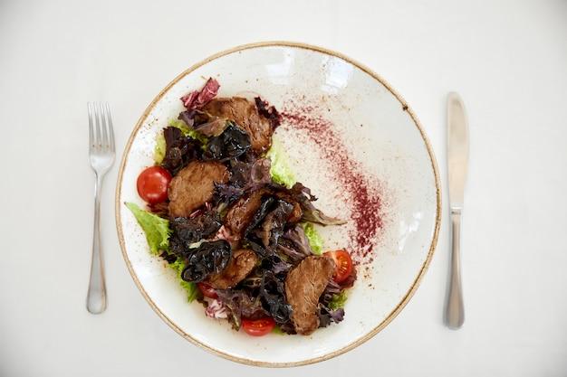 Topview de salada de carne servida com um tomate cereja e alface na mesa branca