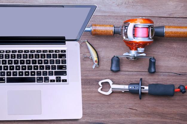 Topview laptop e equipamento de pesca - baitcasting reel, pinça e isca em fundo de madeira.
