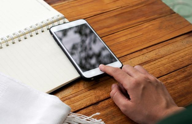 Toque da mão na tela telefone inteligente móvel na mesa de madeira