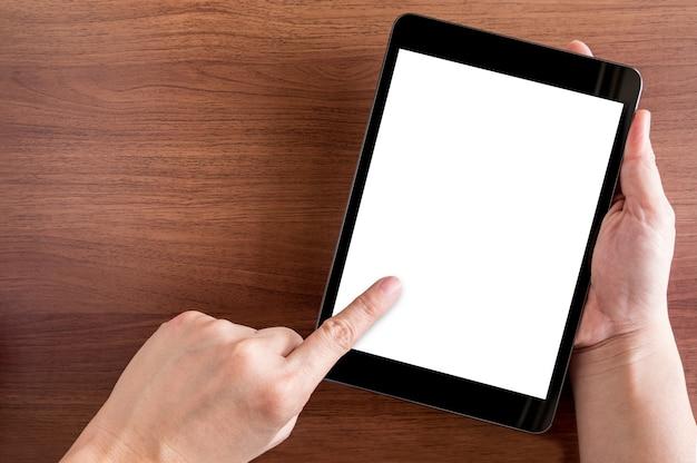Toque de mão na tela vazia do tablet acima da mesa marrom