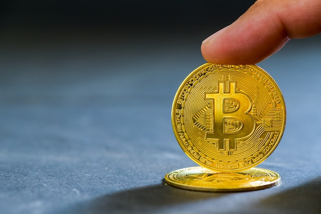 Toque do dedo na moeda de bits em fundo preto, dinheiro eletrônico virtual