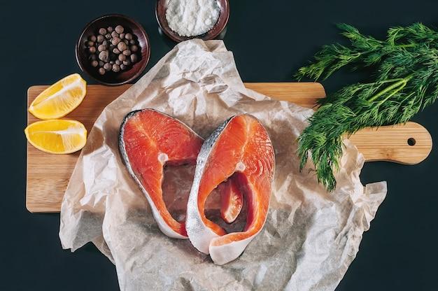 Toque em bifes de peixe com especiarias, limão e ervas em um fundo escuro.
