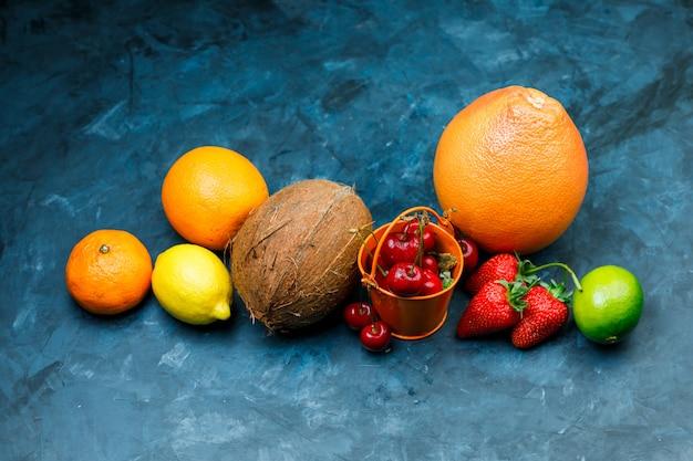 Toranja com laranja, limão, limão, morango, cereja, tangerina, coco deitado sobre uma superfície azul suja