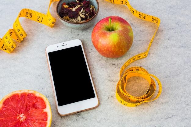 Toranja cortada ao meio; frutas secas; maçã; fita métrica e smartphone em pano de fundo cinzento