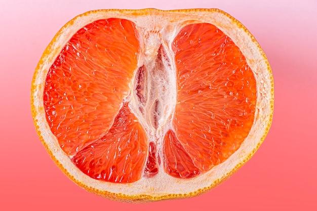 Toranja de corte vermelha fresca na superfície rosa. conceito de saúde feminina. fruta como símbolo da vagina. fechar-se.