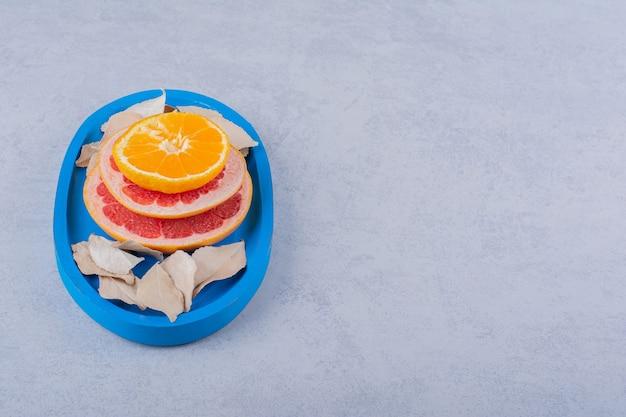 Toranja fresca, anéis de limão e laranja na placa azul.