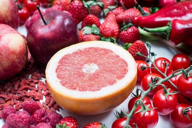 Toranja fresca cortada ao meio e outras frutas vermelhas e legumes