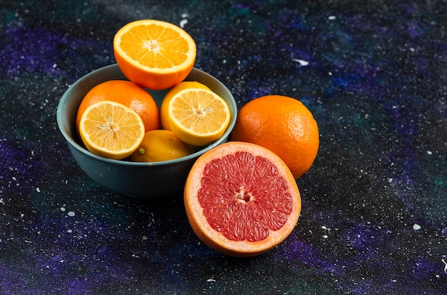 Toranja fresca, limão e laranja em uma tigela e sobre o solo.